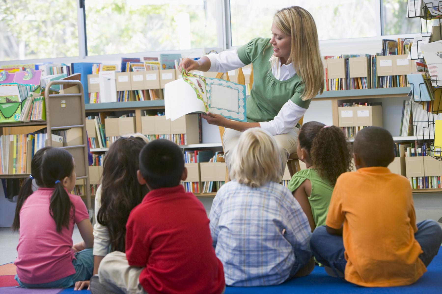 2126420-kindergarten-teacher-reading-to-children-in-library